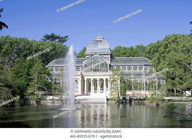 View across the lake to Palacio de Cristal, or Crystal Palace, designed by architect Ricardo Velazquez Bosco (1887), Buen Retiro Park, Madrid, Spain