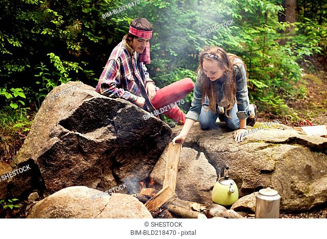 Couple building campfire in forest