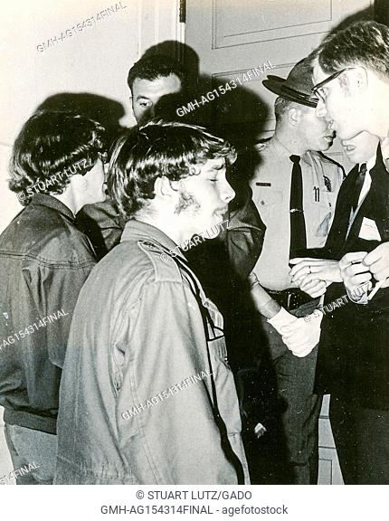 Students wearing hippie attire speak with sheriff's deputies in uniform during an anti Vietnam War student sit-in protest at North Carolina State University