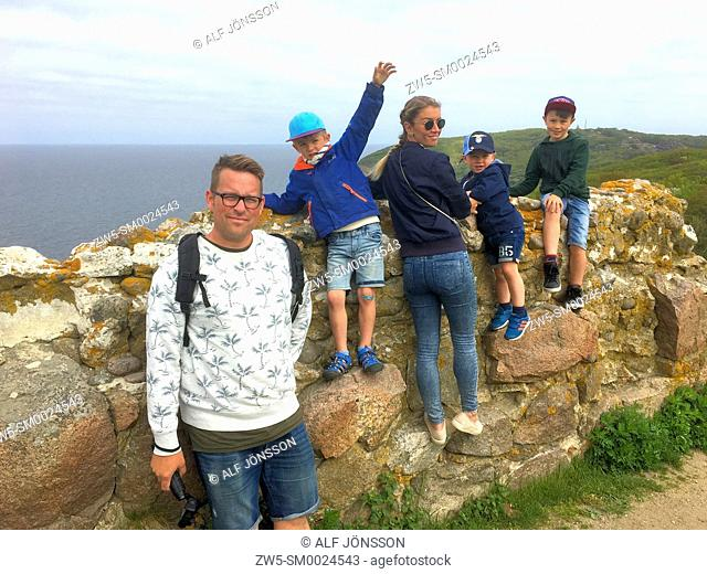 Family standing on the ruin of Hammershus fortress on Bornholm, Denmark, Northern Europe