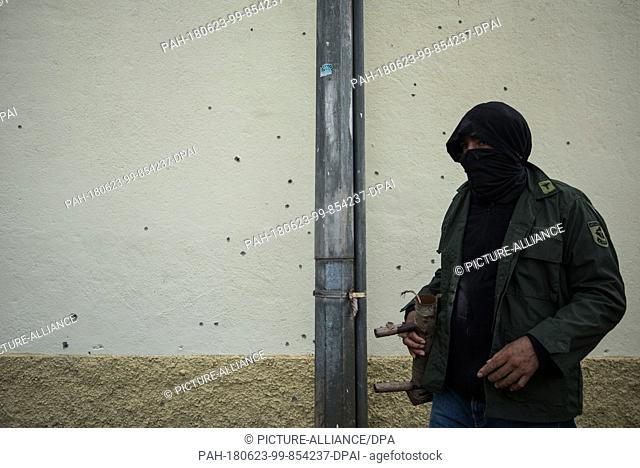 23 June 2018, Nicaragua, Managua: A student leans on a wall with plenty of bullet holes. Paramilitaries stormed the National Autonomous Universities of Managua