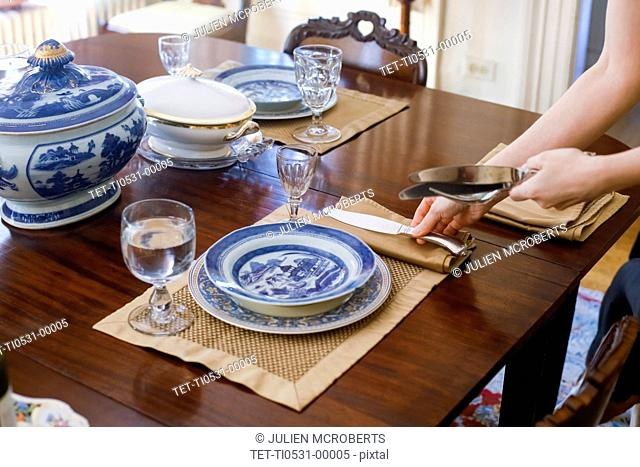 Woman's hands setting table with antique tableware