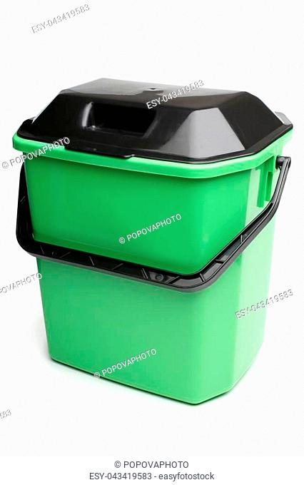 Green plastic bucket with lid on white background