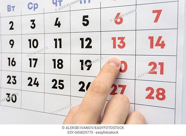 Hand pointing to the day off Saturday on a wall calendar
