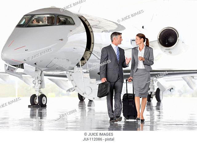 Businesswoman and Businessman leaving private jet