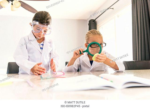 Girls using magnifying glass from chemistry set