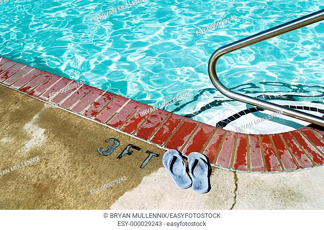 Sandals next to edge of pool