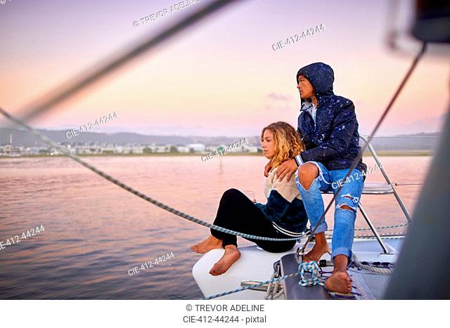 Young couple relaxing on boat at sunset