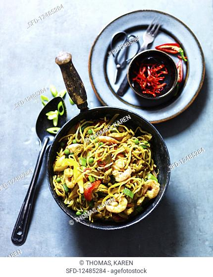 Singapore noodles with fish, shrimp, chili peppers, peas and peppers (Asia)