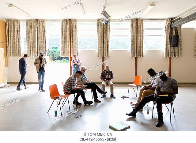 Men waiting, using smart phones in community center