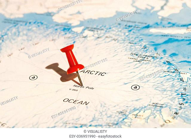 Centre of North Pole marked on map with red pushpin. Selective focus on the word North Pole and the pushpin. Pin casts harsh shadow to the left