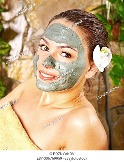 Beautiful woman having clay facial mask apply by beautician