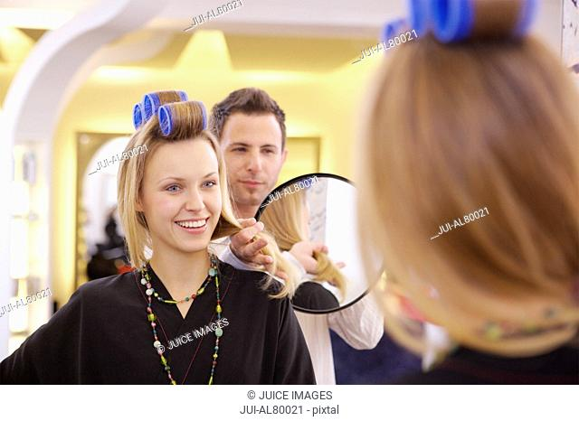 Woman with curlers and mirror in beauty salon