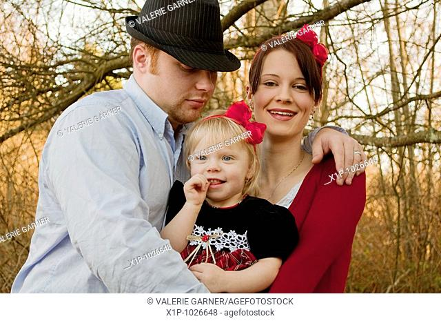 This cute young family is a father embracing his wife and young daughter and they are both wearing red bows in their hair Background is intentionally blurred...