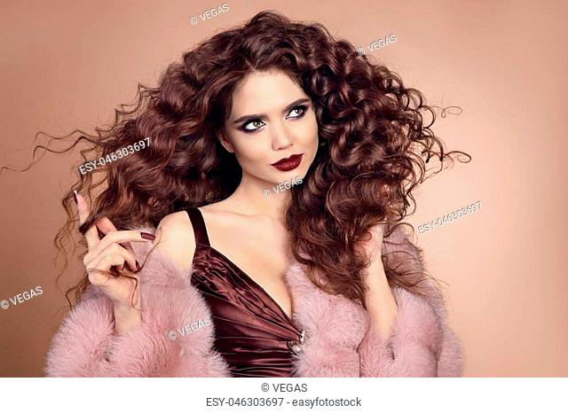 Healthy hair. Glamour portrait of beautiful brunette woman model with marsala matte lips and long curly hairstyle in luxury fur coat isolated on beige...