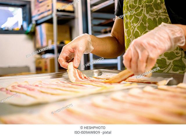 Employee in general store preparing bacon in kitchen