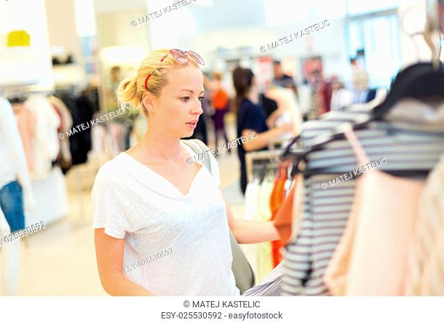 Woman shopping clothes. Shopper looking at clothing indoors in store. Beautiful blonde caucasian female model wearing casual clothes and fashionable sunglasses