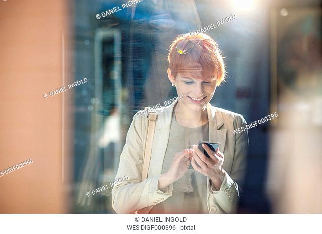Smiling young woman using cell phone at shop window