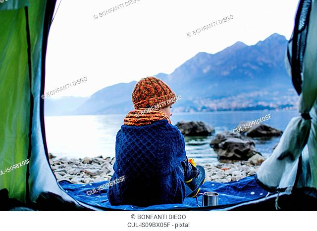 Boy sitting on blanket by tent, rear view, Lake Como, Onno, Lombardy, Italy