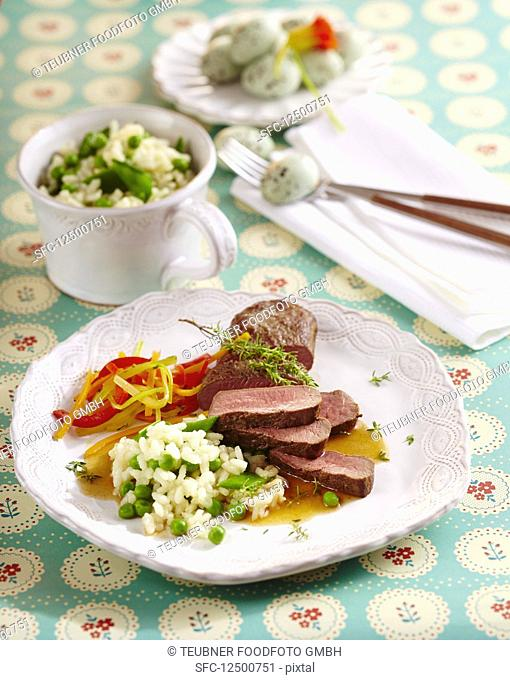 Roast saddle of lamb with a pea risotto and julienned vegetables for Easter