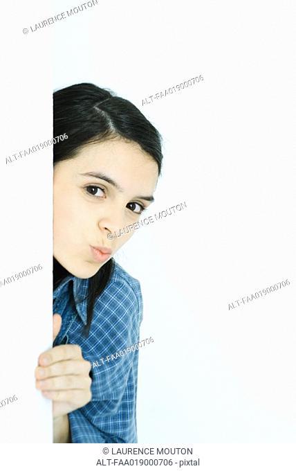 Teen girl peeking around wall, puckering at camera