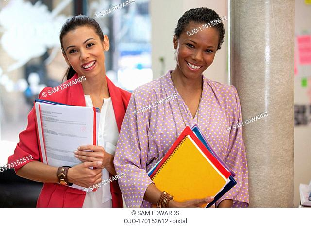 Portrait of smiling businesswoman with folders