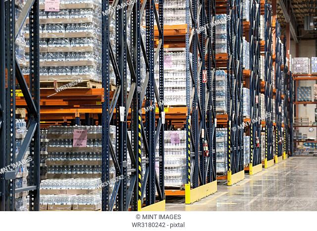 Interior of a warehouse showing flavoured bottled water stored on pallets and set on large racks