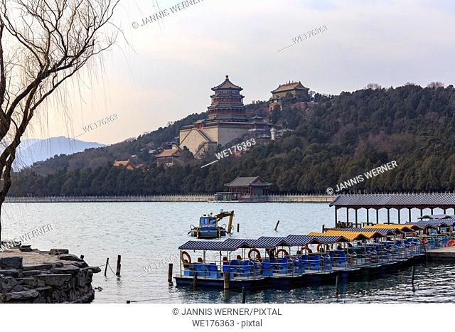 Tower of Buddhist Fragrances and other temples seen past boats from across the lake at the Summer Palace, Beijing, China