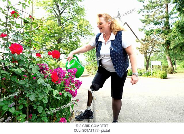 Mid adult woman with prosthetic leg, in garden, watering plants