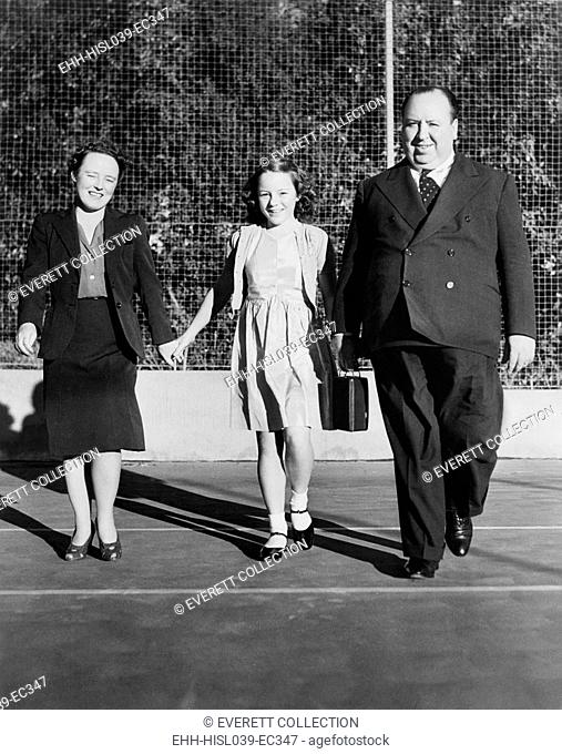 Alfred Hitchcock strolling about the grounds of his Bel Air estate. He is with his wife, Alma Reville, and his daughter, Patricia. Ca