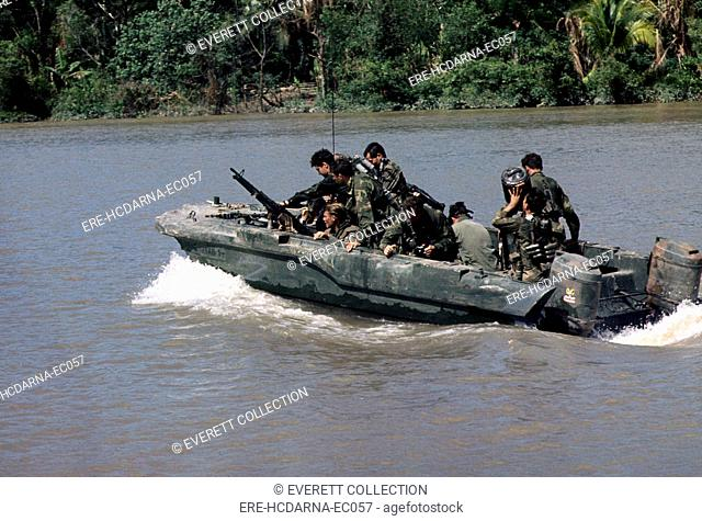 Vietnam War, Republic of Vietnam, members of U.S. Navy Seal Team One move down the Bassac River in a Seal team Assault Boat (STAB) during operations along the...
