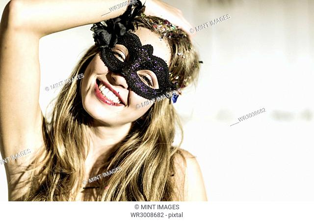 Young woman wearing a mask with confetti in her hair