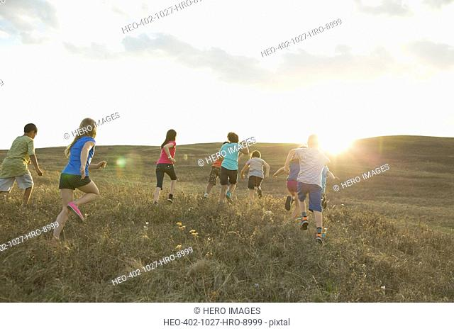 Rear view of playful schoolchildren running on field