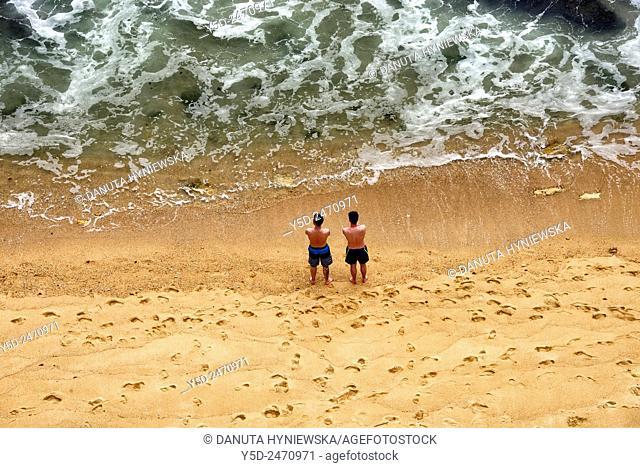 Europe, Portugal , Algarve, Western Algarve, Faro district , Lagos , two men on Camilo beach looking at waters of Atlantic Ocean
