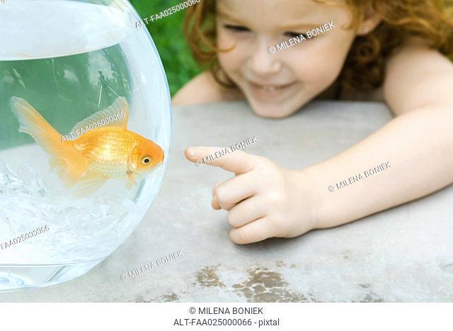 Girl pointing to fish in goldfish bowl