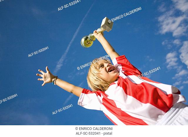 Soccer player cheering with trophy
