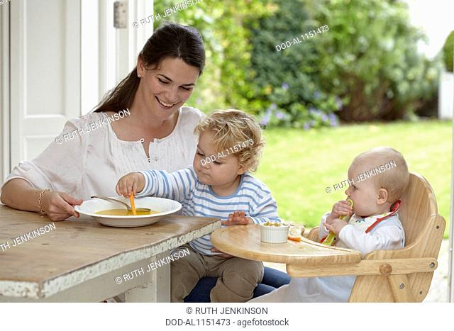 Toddler boy (2 years 4 months) sitting on lap of mother as baby girl sits (9 months) in highchair eating lunch