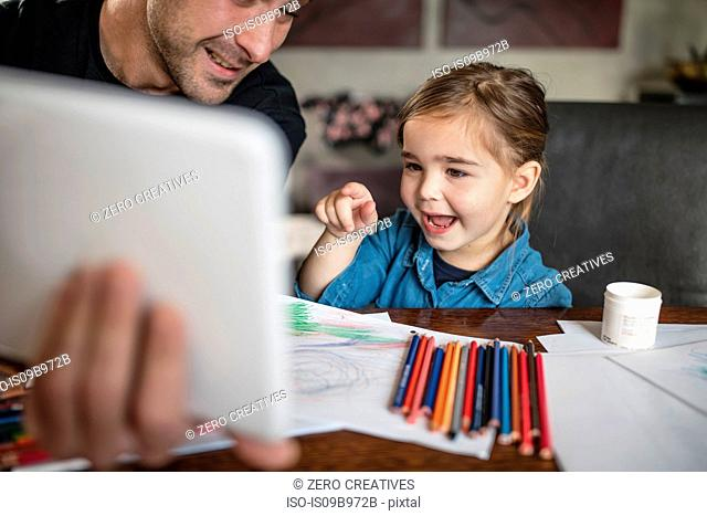 Man with daughter at table pointing at digital tablet