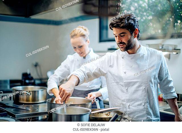 Chefs stirring pots in kitchen