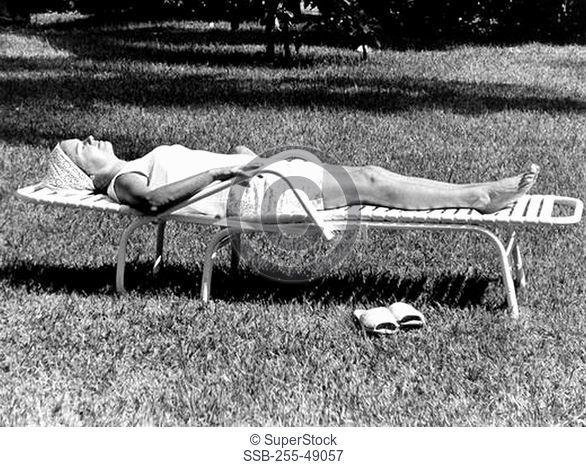 Woman sunbathing in backyard