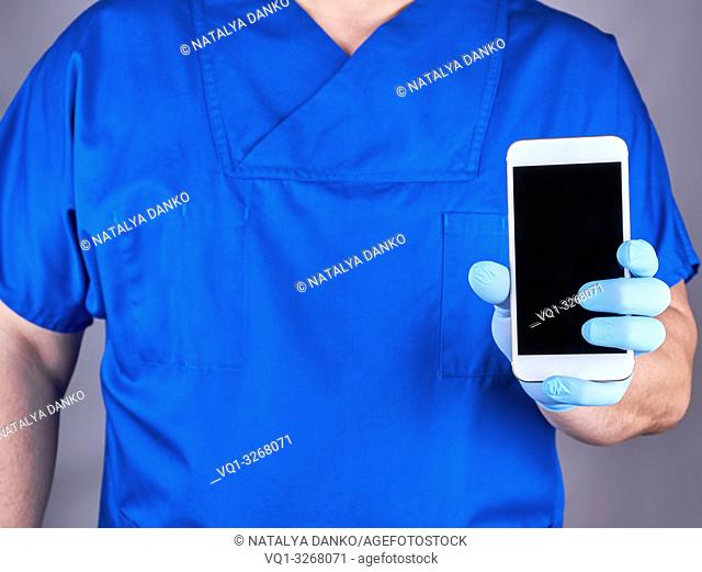 doctor in blue uniform and latex gloves showing a white smartphone with a blank black screen, gray background