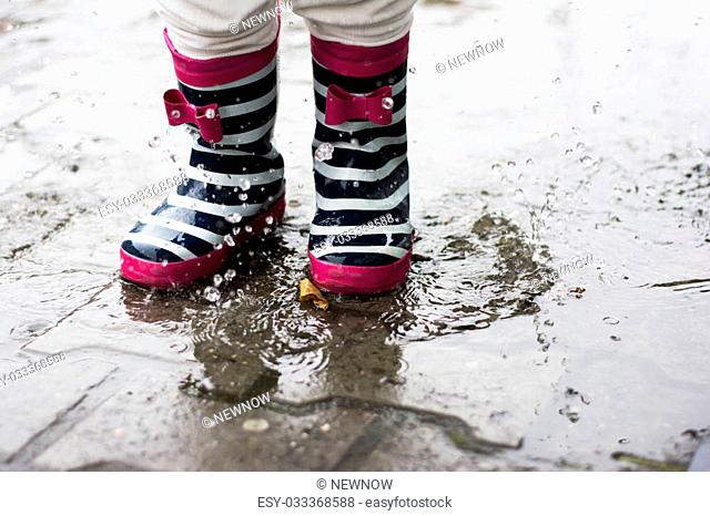 Little girl jumping in a muddy puddles in the rain wearing cute rubber boots