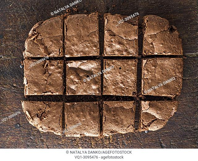 baked rectangular chocolate brownie pie is cut into squares, a wooden brown table
