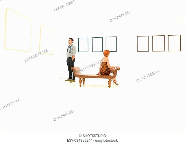 woman and man contemplating empty frames displayed on white walls