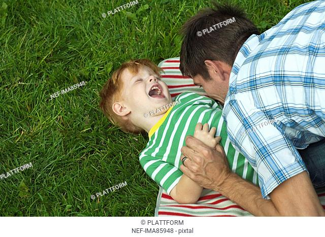 Mid adult father playing with son