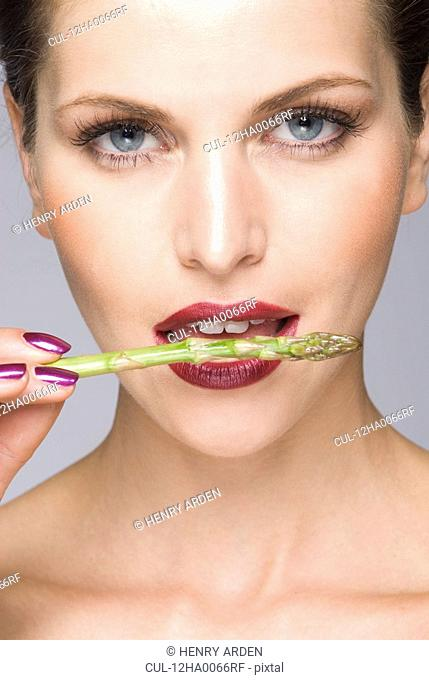 close up of female asparagus in mouth