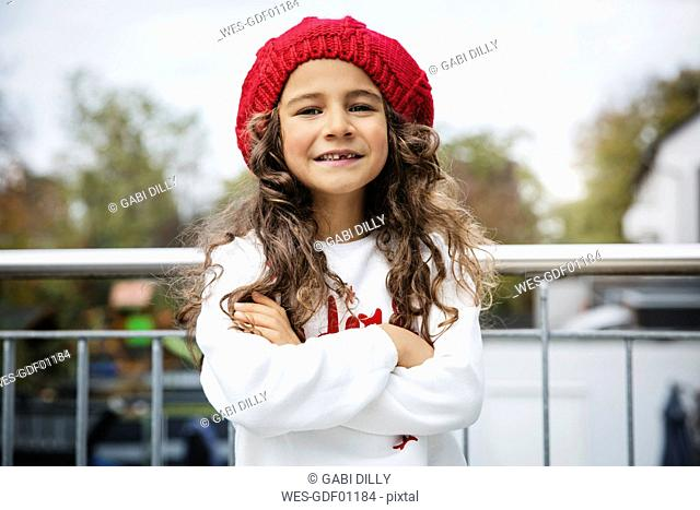 Portrait of smiling little girl with tooth gap wearing red woolly hat