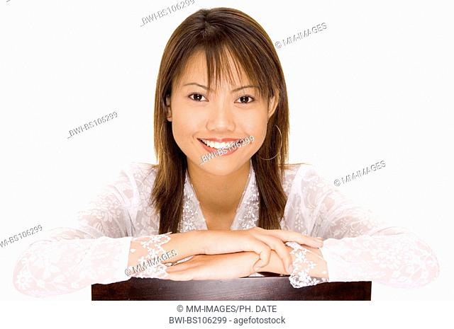A pretty young asian girl with a gerat smile in a white silk blouse