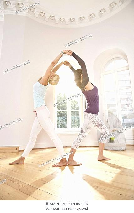 Two women in yoga studio holding a yoga pose with their arms