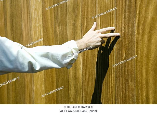 Man touching wood paneling with fingers, cropped view